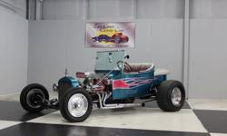 Stk#081 1923 Ford T Bucket Exterior: Fiberglass body with passenger door that opens. Teal paint with silver, light pink flames from front to back. Teal radiator reservoir. Mini headlights in stainless steel mounted on Billet mounts. Stainless windshield