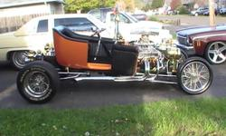 This 1927 vintage tin custom Ford T bucket has a professionally done custom interior, 350 Chevy engine, Ford 9 rear end, Halicrafters front wheels and true spoke rear wheels. The paint job is candy pearescent tangerine and there are no scratches or rock