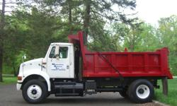 1995 International dump truck, white cab, red dump body. Truck purchased from Beltway International in 2005 with a rebuilt M11 Cummins Turbo diesel, a fresh professionally installed dump body, and a rear end overhauled by E&M machinery Inc. 9 Speed