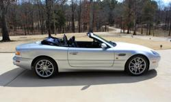 2002 Aston Martin Vantage Volante convertible. The color is Argento Nurburgring (silver), with Caspian Blue interior and soft top, Only 29,100 miles. 5.9L V12, 420 HP, 5-speed Touchtronic automanual transmission, plush leather, burl wood dash, 6 way power