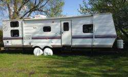 30 foot travel trailer- sleeps 9. Front bedroom with queen bed, back has bunk with full bed on bottom and twin on the top. Has kitchen/living room 14 ft. slide out. Both table and couch pull out to double size beds. New 18 ft. awning. Newer tires are in