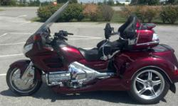 This 2009 Roadsmith Goldwing GL18HPM trike is loaded, has Independent Rear Suspension, driver backrest, premium audio, cb radio, passenger armrests, cruise control, reverse, wing guards, highway pegs parking brake, and trailer hitch!