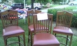 Four solid wood leather seat bar stools, good condition.