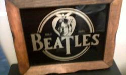 Beatles picture in a frame from 1940 to 1980 on a black backround with gold color
