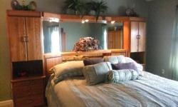 Solid oak contempary Michael Howard bedroom suite...unusual headboard composed of 5 pieces...headboard, triple mirror w/lights and bridge that connects two 6 foot pier cabinets on each side. Triple dresser and large armoire. Storage galore. What makes