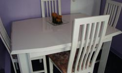 I have a white lacquered finish dining room table with 4 matching chairs for sale. The table measures 52 inches long by 30 1/4 inches wide. It has an extension which measures 30 1/4 inches. The top part on the back rests of 2 chairs need a little touch up