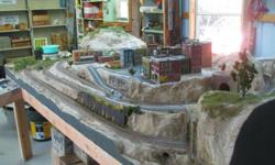HO train on 4' X 8'plywood table,Woodland Scenics, Riverpass layout. Extra 3' track sections, buildings, Woodland Scenics landscape materials including trees, people, cars, Hydrocal, glue, glue guns, and lots more.For a