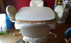 Cream/White colored table (leaf included but not shown), with four leathery/coushion style seats that are adjustable. Table has a wooden lined edging while chairs have wooden arms and wood on the bottom.  CASH ONLY   AND YOU