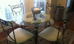 Kitchen / Dining Room Table For Sale Painted wrought iron round glass table with four (4) chairs is for sale. The table has a beveled round glass that measure 44 inches in diameter. The table includes four (4) wrought iron chairs that have an off-white (