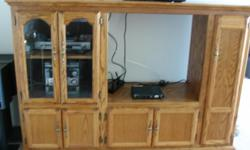 "This is a solid Medium Oak Entertainment Stand. The stand measures 71"" Long x 48-1/2"" Tall x 20"" Wide. The stand has a 3 shelf glass enclosed cabinet with removable shelves for DVD, stereo, etc. The stand also has two sets of bottom cubboards for"