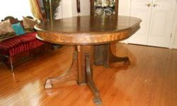 44? round solid wood table with two custom made 10-1/2? wide leaves with matching apron. Circa 1870. Table can extend to 100? (8 ft and 4 inches). Underneath has been fortified with some new wood for stability. Has age appropriate wear. Delivery is not