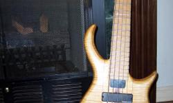 1996 Custom built Warrior Bass Guitar with flame maple natural wood body. 1 piece design neck, 5 string, with base line electronics. Number #133 built by Warrior Instruments when company was started. Purple heart wood limated into a stripe runs down the